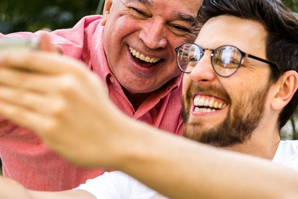 """An older man and young man with glasses are smiling and laughing while taking a """"selfie"""" photo on a smartphone"""
