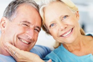Closeup portrait of a smiling retired couple against bright background